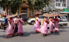 Buddistiska nunnor som går för morgonallmosa på gatan i Mandalay, Myanmar Royaltyfri Bild