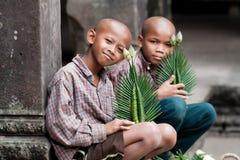 Buddistiska pojkar som säljer det blommaAngkor Wat tempelet Fotografering för Bildbyråer