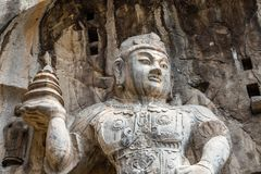Buddistiska skulpturer i den Fengxiangsi grottan, Luoyang, Kina Fotografering för Bildbyråer