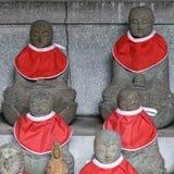 BUDDISTISKA STATYER I JAPAN BÄR RÖDA KRAGAR Royaltyfria Bilder