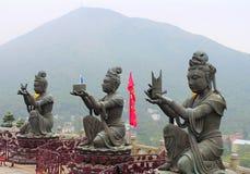 Buddistiska statyer som gör offerings till den stora Buddha, Hong Kong Arkivfoto
