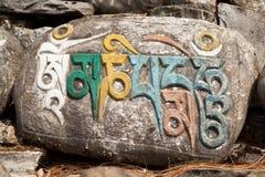 Buddistiska symboler på Mani Wall i den Manang dalen, Annapurna strömkrets, Manang, Nepal Royaltyfri Fotografi