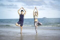 Buddy athlete woman and man doing yoga and stretching body on summer tropical island beach with blue sea, sport woman and man