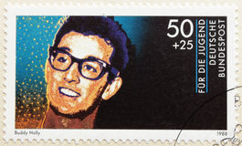 Buddy Holly. GERMANY - CIRCA 1988. A postage stamp printed in Germany shows image portrait of famous American singer- songwriter and pioneer of rock and roll stock images