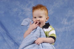 Buddy laughing. Redhaired boy with blanket laughing Stock Photo