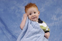 Buddy loves his blanket. Redhaired boy loving his blanket Stock Photography