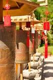 Buddyjscy modlitewni koła przed świątynną złoto statuą goddes Guanyin w Nanshan parku Na modlitewnych kół mantrze obrazy stock