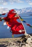 Buddyjska modlitwa zaznacza na wiatrze przeciw błękitnemu jezioru Fotografia Royalty Free