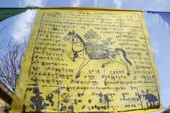 Buddyjska tibetan modlitwa zaznacza falowanie w wiatrze przeciw niebieskiemu niebu obrazy stock