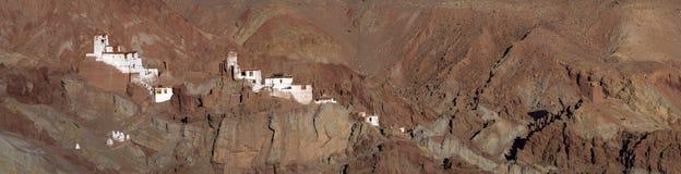 Buddyjski monaster Basgo Gonpa, panoramiczna fotografia: biali budynki monaster lokalizują wśród wysokiego Burgundy mountai Fotografia Stock
