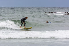 BUDE, CORNWALL/UK - 13 AGOSTO: Praticando il surfing a Bude in Cornovaglia su A Fotografie Stock