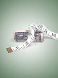Bank's Interest Rates, Annual Budget. Money is tight, measuring tape wrapped around an American one dollar bill isolated on a light green background Stock Images