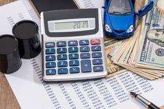 Budget annuel de pétrole, de voiture de jouet, d'argent et de calculatrice image stock