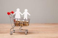 Budget av familjen Shoppingvagn mycket av mynt och familjsymbolet från män och kvinnor royaltyfri bild