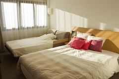 Budget bedroom with two beds with red pillows and window. Simple budget bedroom with two beds with red pillows and window Stock Photos