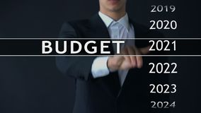2023 budget, businessman selects file on virtual screen, annual financial report. Stock footage stock video footage