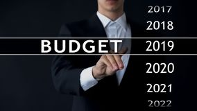 2019 budget, businessman selects file on virtual screen, annual financial report. Stock photo royalty free stock images