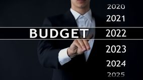 2022 budget, businessman selects file on virtual screen, annual financial report. Stock photo royalty free stock image