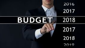 2018 budget, businessman selects file on virtual screen, annual financial report. Stock photo royalty free stock photo