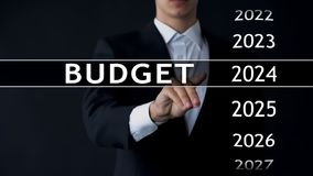 2024 budget, businessman selects file on virtual screen, annual financial report. Stock photo stock images