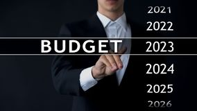 2023 budget, businessman selects file on virtual screen, annual financial report. Stock photo royalty free stock photography