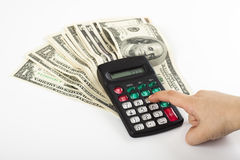 Budget calculating. A child calculating expancess on a calculator that stands on  a couple of dollars Stock Images