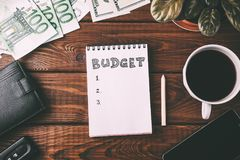 Budget checklist on blank notepad with pouch, coffee, pen, money and smart phone. Budget checklist on blank notepad with pouch, coffee cup, pen, money and smart stock photography