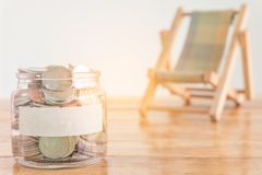 Budget concept, money savings concept. Collecting money in the money jar for your concept. Money jar with coins and beach seat on. Budget concept, money savings royalty free stock images