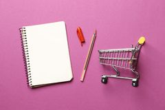 . Budget concept. shopping cart,  blank paper notebook stock photo
