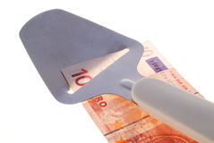Budget cut. Cheese slicer, slicing a 10 Euro note against a white background stock photos