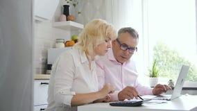 Budget de comptabilité de couples mûrs de famille dans la cuisine confortable banque de vidéos