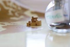 Budget de voyage - l'épargne d'argent de vacances dans un pot en verre sur le monde m Photographie stock libre de droits