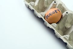 Budget egg in paper tray as a recession concept Stock Photos