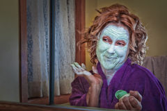 Budget Facial. Woman in front of bathroom mirror with a do it yourself facial mask stock photography