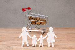 Budget of the family. Shopping cart full of coins and family symbol. From dad, mom, son and daughter Stock Photography