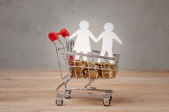 Budget of the family. Shopping cart full of coins and family symbol from men and women.  Stock Photo