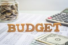 Budget and financial management for business project. Wooden alphabet word Budget putting on accounting stagement and paperwork with money saving jar royalty free stock photos