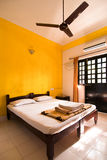 Budget hotel room. A budget hotel room with yellow walls and a fan Royalty Free Stock Photos