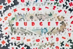 Budget idea, abundance white puzzle jigsaw with alphabets combine word BUDGET and other letter pieces around on banknotes and dar stock photography