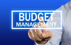 Budget Management Concept. Business concept image of a businessman clicking Budget Management button on virtual screen over blue background Royalty Free Stock Images
