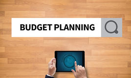 BUDGET PLANNING. On the tablet pc screen held by businessman hands - online, top view royalty free stock photography