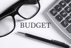 Budget. Sing on table, glasses, pen, calculator royalty free stock images
