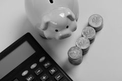 Budget and tax payments concept. Piggy bank and coins. Budget and tax payments concept. Piggy bank stands next to stacks of coins and calculator. Investments and Stock Photo