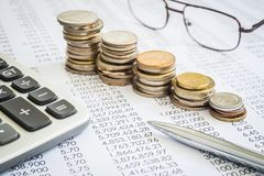 Budget and tax planning with raising coin stacks. Closeup the silver modern pen on financial and accounting reports with increase coin stacks, glasses and royalty free stock images