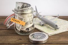 Budget Travel concept. Travel money savings in a glass jar with toy aircraft on world map and compass. To save for the trip Stock Photography
