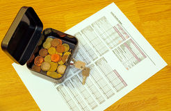 Budget worksheet and coins. Coins in box with key on a monthly budget planning worksheet Royalty Free Stock Photos
