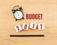Budget 2017 year on wood cube with pencil and clock top view on Stock Image