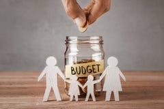 budgeter Den Glass kruset med mynt och en inskrift är budget- och symbolet av familjen med barn Manhållmyntet i hand royaltyfri fotografi