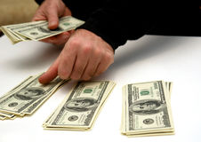 Budgeting. Man counting out hunderd dollar bills in three stacks on white table Royalty Free Stock Photo