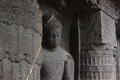 Budha holding flower. This picture has been taken from one of the caves in Ajanta, Aurangabad. This picture shows the floral carvings upon the pillars and the Stock Image